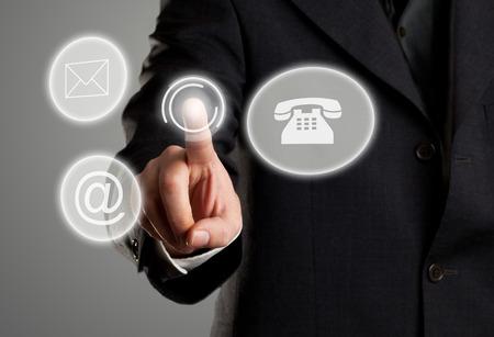 Businessman berühren virtuellen futuristischen Display mit Symbolen für Telefon, Post und E-Mail-Kontaktinformationen