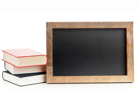 books on a wooden surface: Empty clean old chalkboard with books on white background Stock Photo