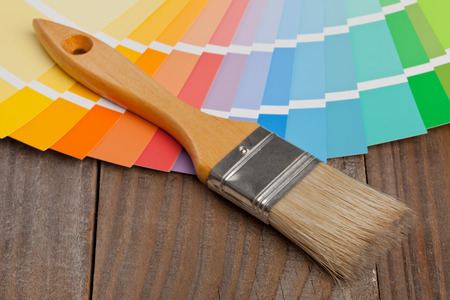 Color chart guide for renovation with brush on wooden surface photo