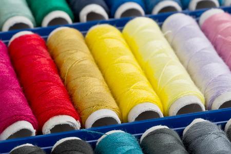 hilo rojo: Colorido surtido de rollos de hilo de coser en caja Foto de archivo