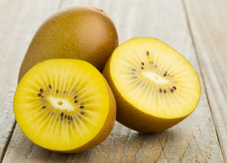 Whole and cut golden kiwifruit kiwi (Actinidia chinensis) on wooden cutting board