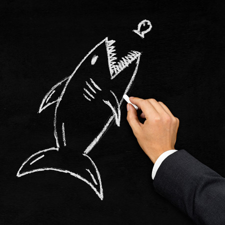 shark: Businessman drawing shark hunting little fish with chalk on blackboard - acquisition, challenge or danger concept Stock Photo