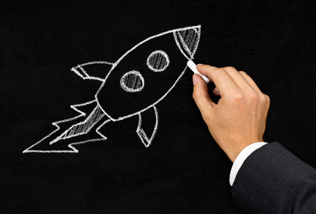 flying man: Businessman drawing cartoon rocket with chalk on blackboard background - innovation, startup or idea concept Stock Photo