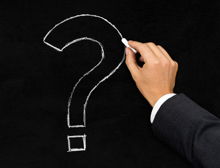 signo de interrogación: Hombre de negocios dibujo signo de interrogación con tiza en fondo de la pizarra