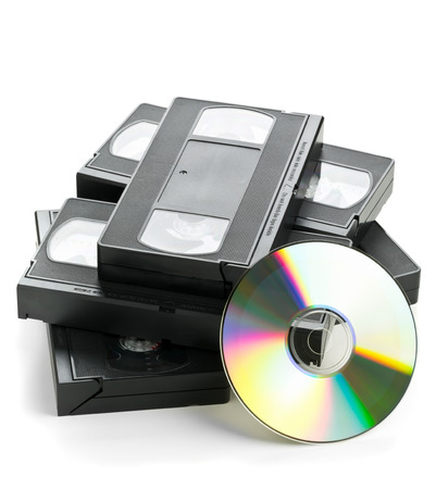 Heap of analog video cassettes with DVD disc - old movies backup or transfer concept Foto de archivo