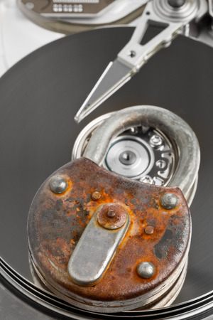 harddrive: Old rusty locked padlock on computer harddrive - information or data security concept