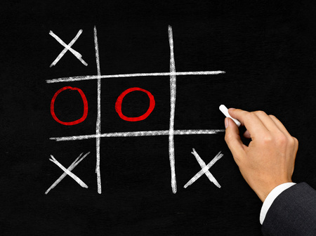 success in business: Man drawing tic-tac-toe game with chalk on blackboard background