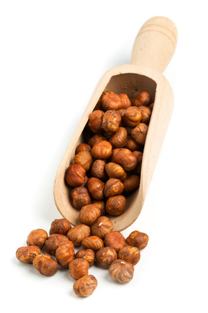 cobnut: Pile of cracked and shelled hazelnut kernels in wooden scoop on white background