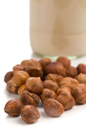 shelled: Glass of almond milk with shelled almond kernels on white background