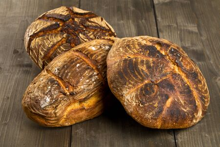 flavours: Home-made bread loaves of different flavours on wooden table background