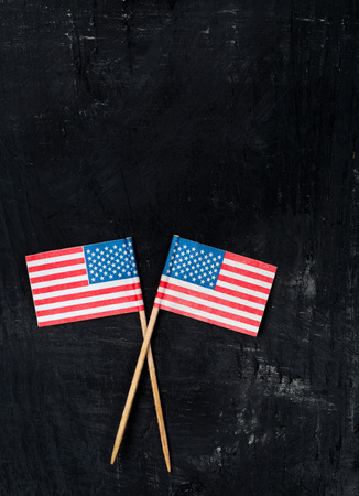to and fro: Two american paper flags fro baking decoration on black wooden background Stock Photo