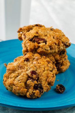 oatmeal cookie: Oatmeal, walnut, raisin and cranberry cookies on blue plate