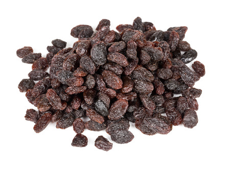 Heap of raisins close up over white background