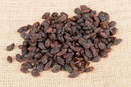 heap up: Heap of raisins close up on brown burlap sack Stock Photo
