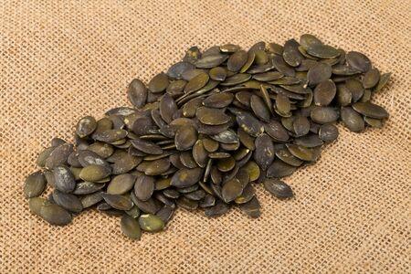Heap of unshelled pumpkin seeds on burlap background Stock Photo