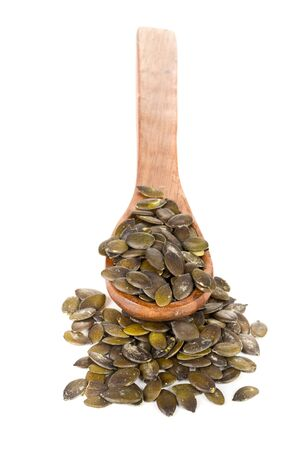 spoons: Unshelled pumpkin seeds in wooden spoon over white background