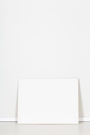 white canvas: Blank canvas leaning against empty white wall