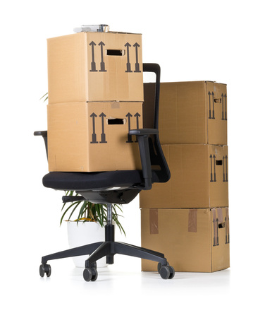 relocation: Movign boxes on  office chair over white background - office moving or relocation concept