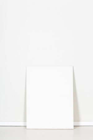 blank canvas: Blank canvas leaning against empty white wall