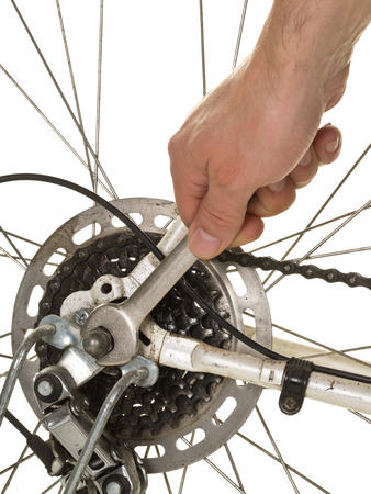 rear wheel: Man repairing rear wheel on a bicycle over white background