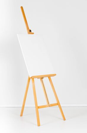 blank canvas: Wooden easel with blank canvas in front of white wall