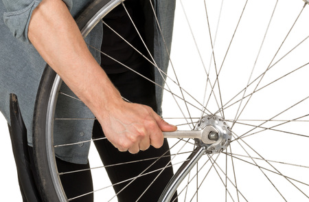 Man repairing front wheel on a bicycle over white background