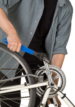 pedals: Man fixing pedals on a bicycle over white background