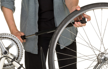 refilling: Man refilling front tire on a bicycle - bicycle service concept