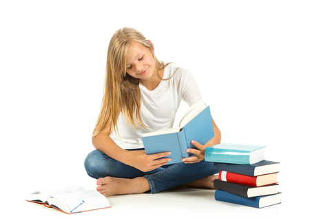 Young girl sitting on the floor with books reading over white background