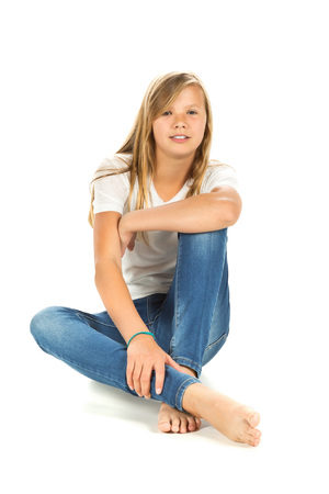 jean: Young girl sitting barefoot with white t-shirt and blue jeans over white background