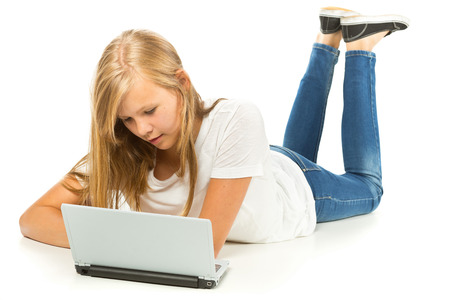 young girl barefoot: Young girl lying on the floor using laptop over white background Stock Photo