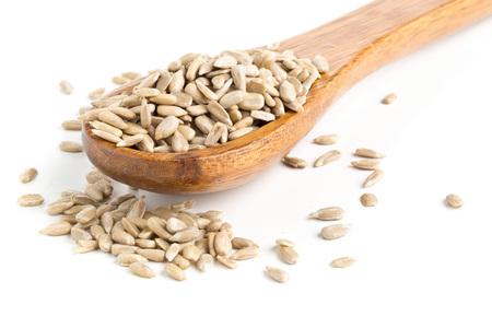 semillas de girasol: shell semillas de girasol naturales en cuchara de madera sobre fondo blanco Foto de archivo