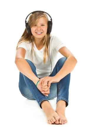 Niña sentada en el suelo escuchar música con auriculares sobre el fondo blanco