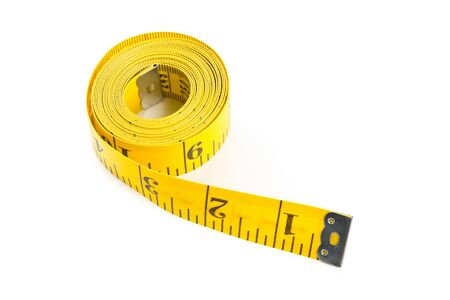 measurement tape: Coiled up yellow measurement tape over white background