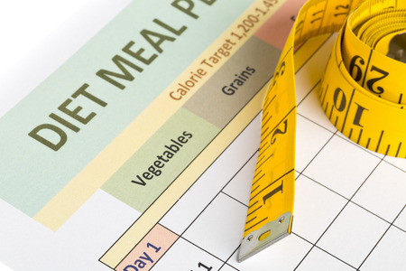 Measurement tape on diet meal planner sheet - dieting or weight loss concept Stock Photo