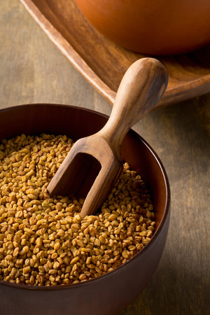 unprocessed: Whole unprocessed fenugreek (Trigonella foenum-graecumcumin) seeds in wooden bowl with scoop