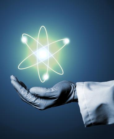 Chercheur ou scientifique avec gant de caoutchouc tenant le modèle de l'atome lumineux sur fond bleu Banque d'images - 69787111