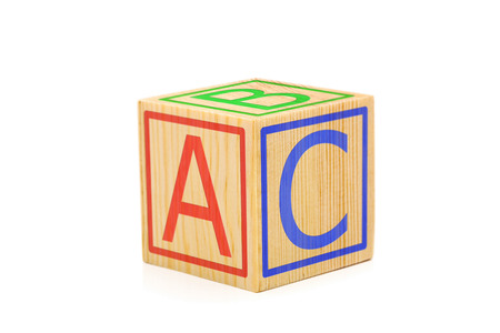 Letters A, B and C imprinted on sides of single brown wooden cube on white background