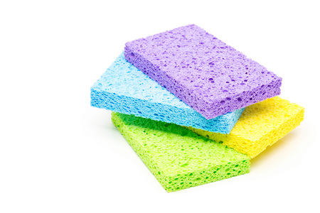 Stack of unused, clean green, yellow, blue and violet cleaning sponges over white background