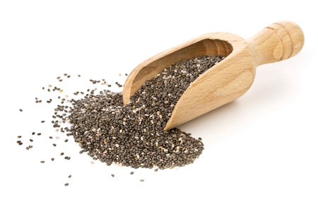 Whole dried black chai seeds in wooden scoop on white background Stock Photo