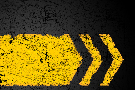 Grunge distressed yellow direction road marking on dark metal background