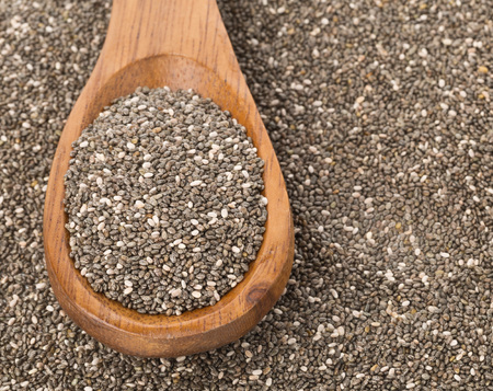 unprocessed: Raw unprocessed black chia seeds on wooden spoon on chia seed background