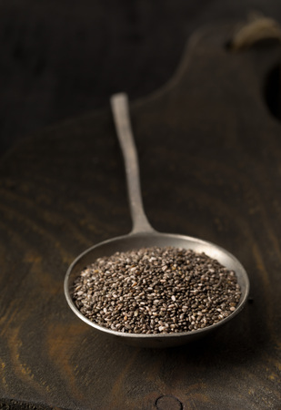 unprocessed: Raw unprocessed black chia seeds in metal spoon on wooden board over dark background