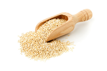 unprocessed: Raw, whole, unprocessed quinoa seed in wooden scoop over white background