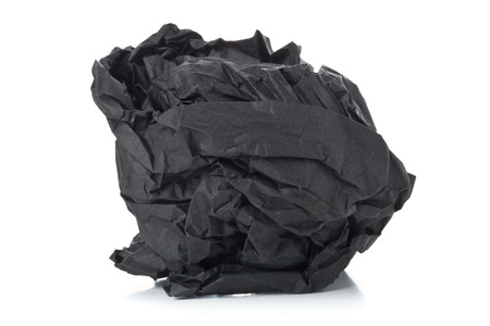 Crumbled black paper ball on white background - waste or fail concept