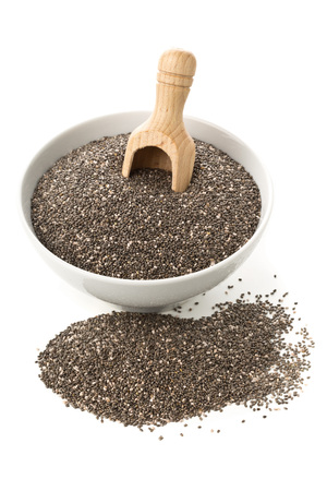 unprocessed: Raw, unprocessed, dried black chia seeds in white bowl with wooden scoop on white background Stock Photo