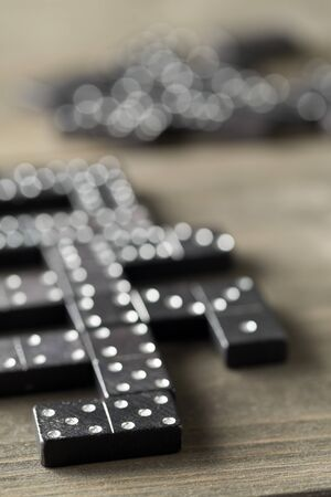 Game of domino with domino stones on wooden background; selective focus on domino stone in front Stock Photo