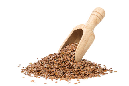 Raw, unprocessed linseed or flax seed in wooden scoop over white background