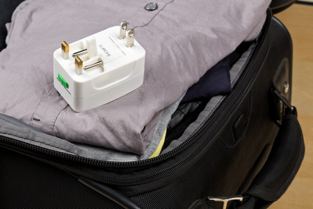 Travel power adapter with connectors for european, UK, and US power plugs on packed suitcase with clothings - travel preparation