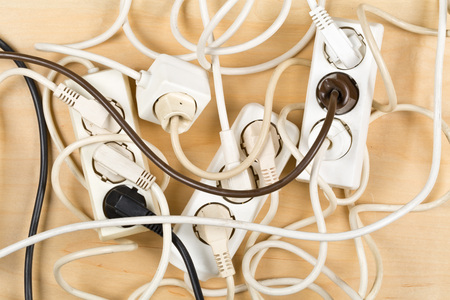 Cable chaos clutter from multiple electric wire extension cords and multi-contact plugs on wooden floor or table background 版權商用圖片 - 81342419